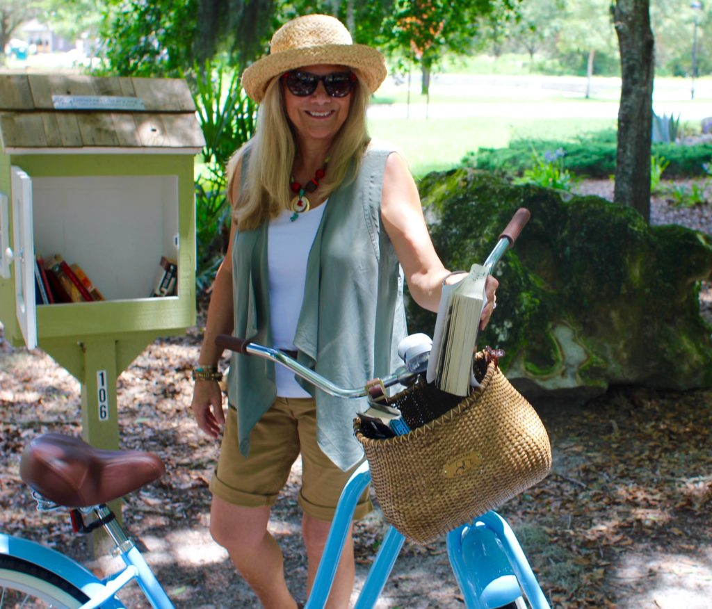 Woman visiting the Little Free Library on a bike.