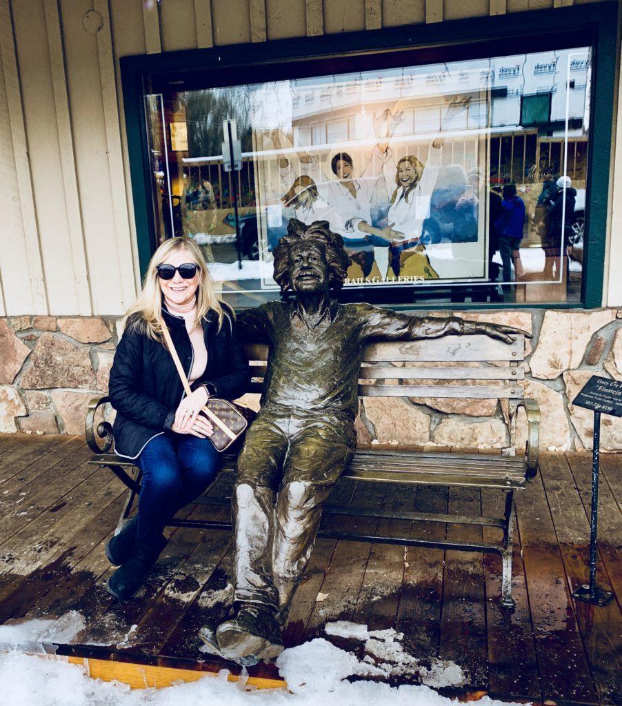 Woman sitting on bench with statue of Albert Einstien.
